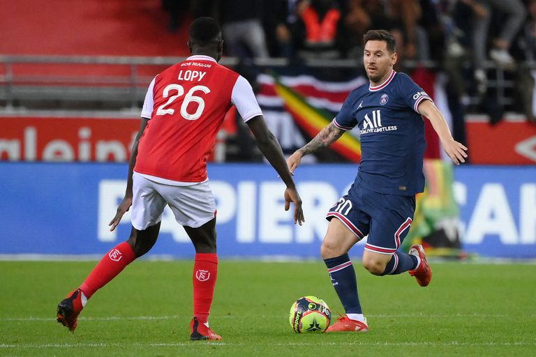 Paris Saint-Germain's Argentinian forward Lionel Messi (R) runs with the ball towards Reims' Senegalese defender Dion Lopy during the French L1 football match between Stade de Reims and Paris Saint-Germain (PSG) at Stade Auguste Delaune in Reims, northern France on August 29, 2021. (Photo by FRANCK FIFE / AFP)