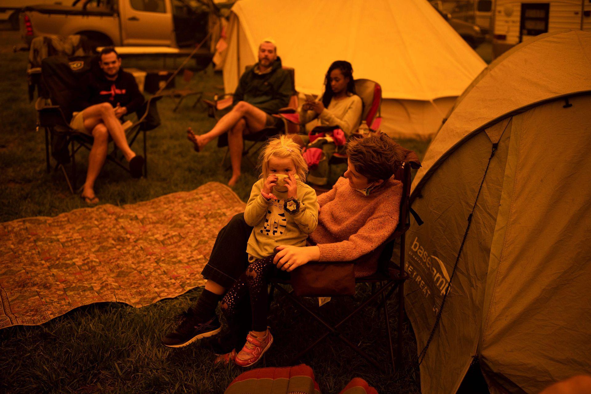 La gente se sienta y espera en un parque de la ciudad de Bega, en el sur de Nueva Gales del Sur, donde acampan después de ser evacuados de sitios cercanos afectados por incendios forestales el 31 de diciembre de 2019.