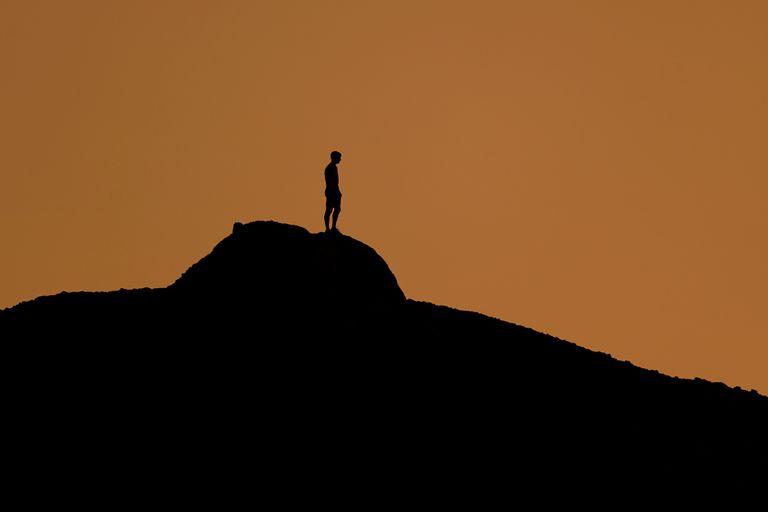 Un hombre observa solo el atardecer en una colina del Papago Park de Phoenix el 19 de febrero del 2021. Mucha gente dice que no tiene casi amigos en los que confiar en casos de emergencia. La pandemia del coronavirus aumentó su aislamiento. (AP Photo/Charlie Riedel, File)