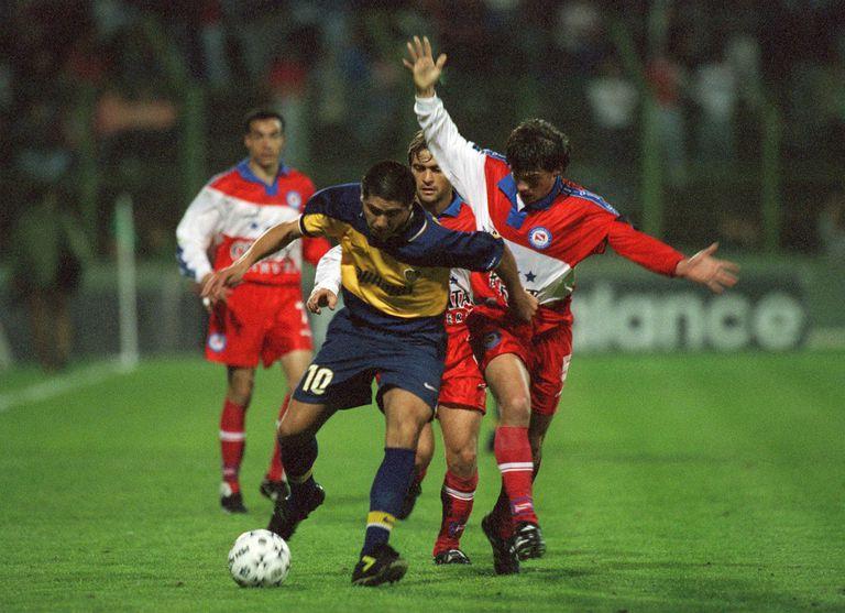 Mariano Herrón, volante central de Argentinos, persiguiendo a Juan Román Riquelme, enganche de Boca, en la cancha de Ferro, por el Apertura 99