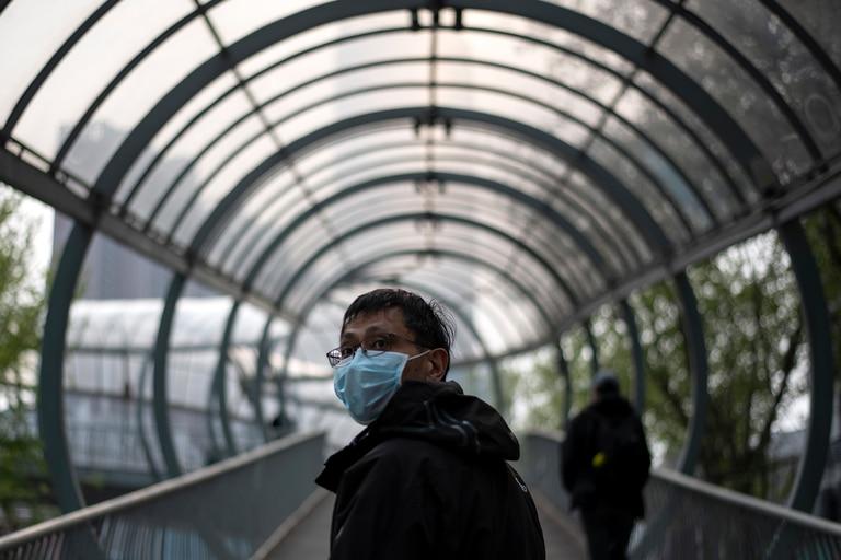 Un hombre con un barbijo camina por un paso elevado en Wuhan, en la provincia central china de Hubei