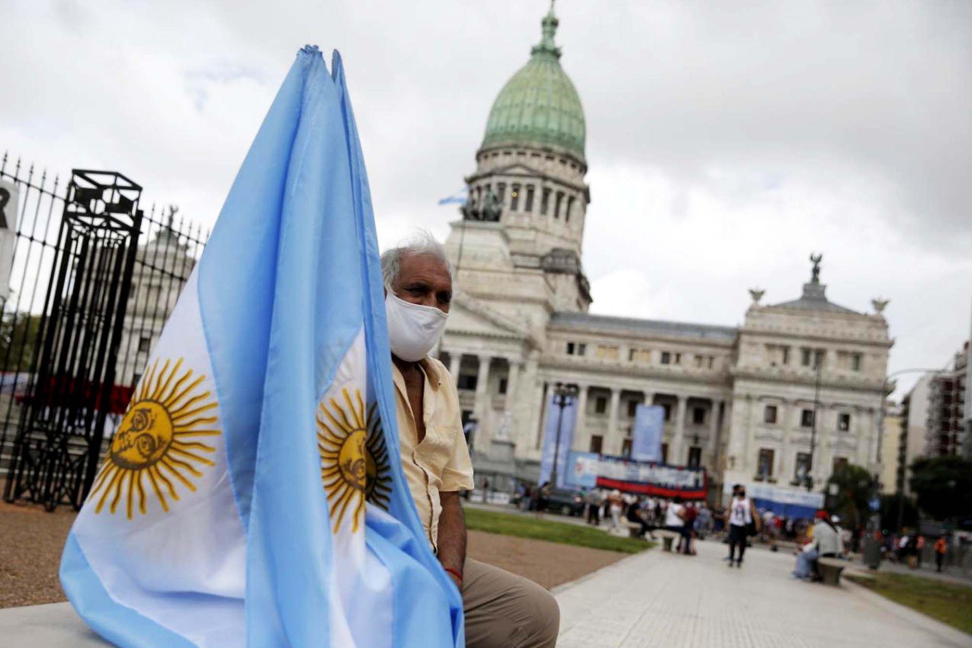 Un hombre con su bandera espera en los alrededores del Congreso la apertura de las sesiones legislativas