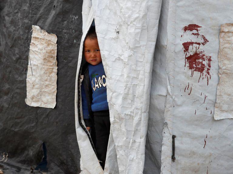 Un niño mira desde el interior de una tienda de campaña en el campamento de al-Roj
