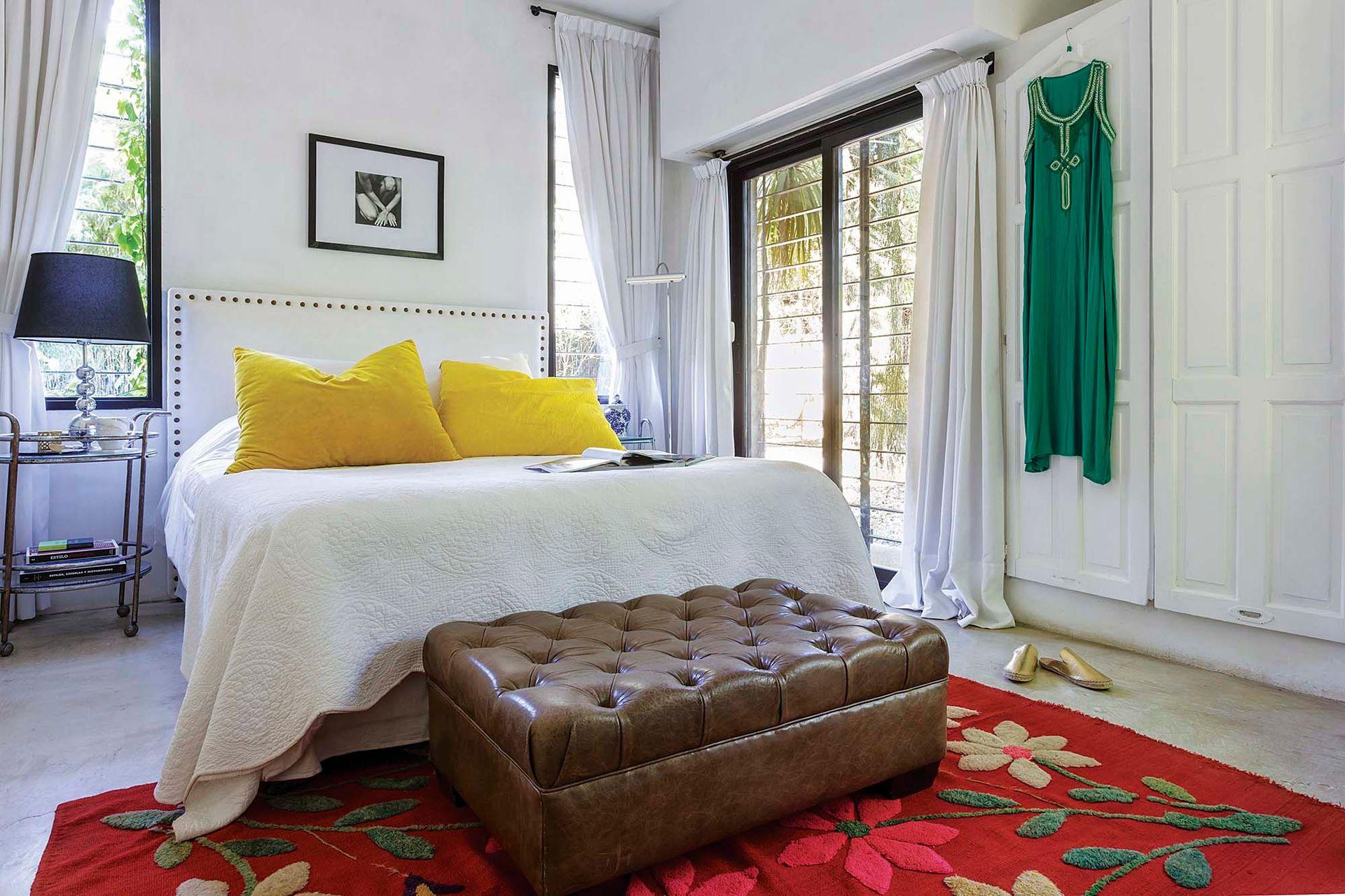 """En la suite, antigua alfombra norteña (El Chaniar) y almohadones amarillos de lino y terciopelo (Capricho #5). """"Su color vibrante te llena de energía, y su tamaño y textura te dan ganas de hundirte en la cama y relajar""""."""