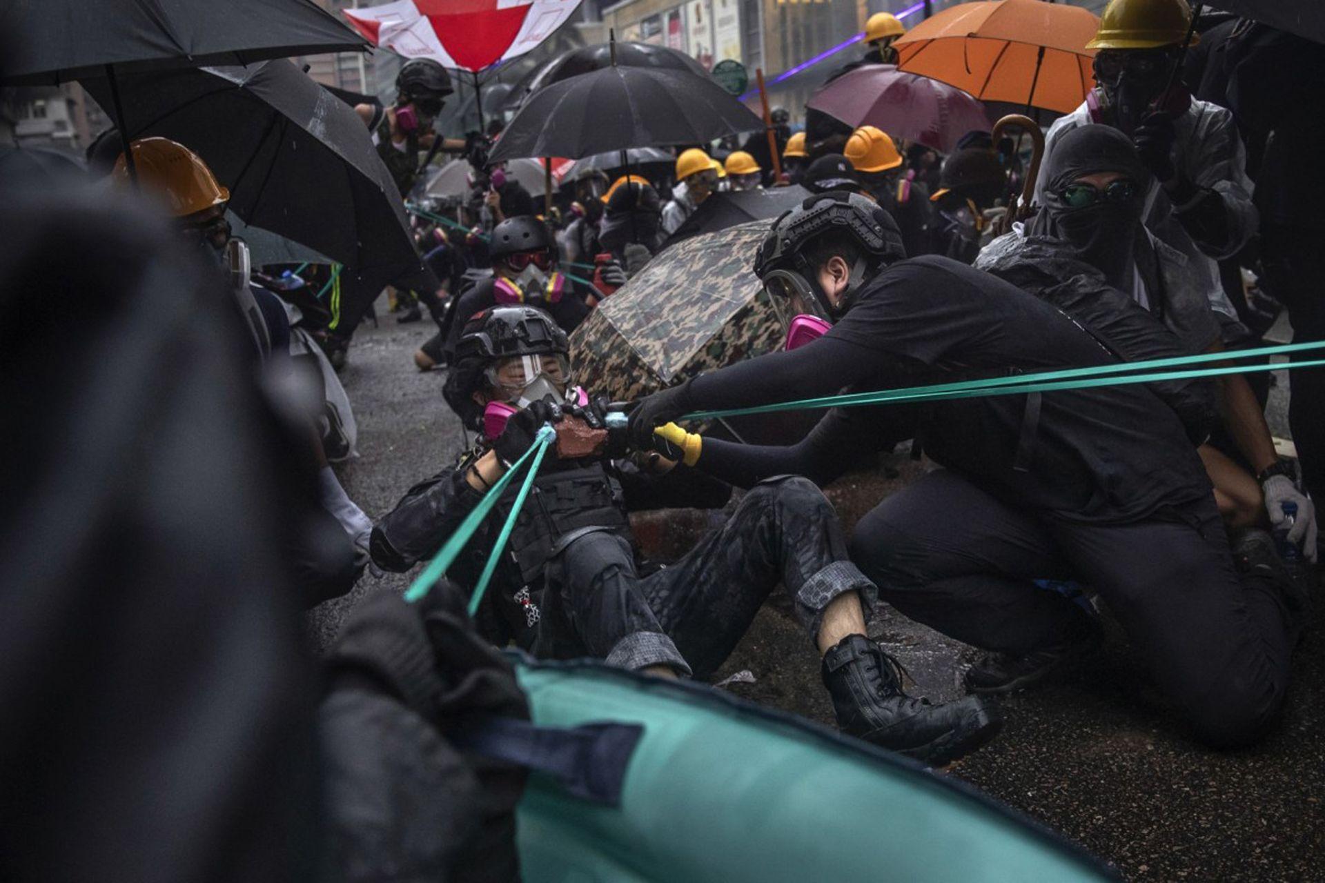 """Los manifestantes usan """"tirachinas"""" para lanzar ladrillos contra la policía"""