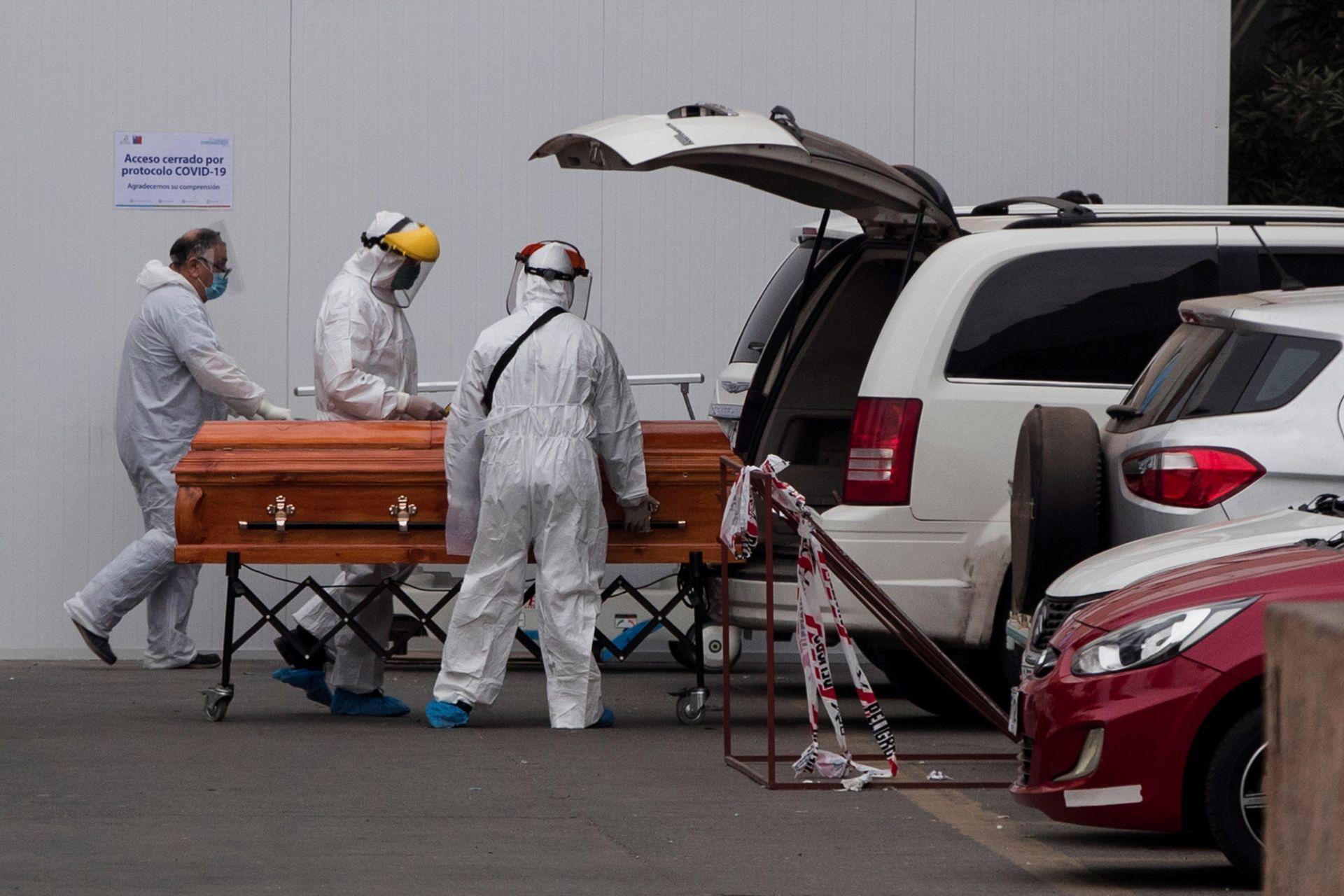 Personal de un hospital de Santiago de Chile lleva un ataúd por el aumento de muertos por coronavirus