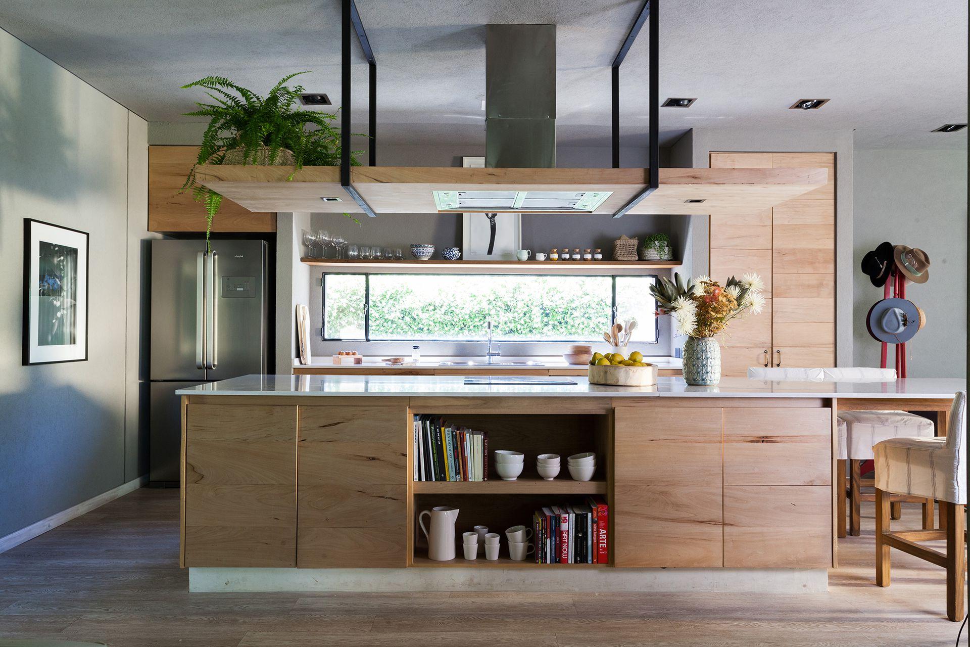 Isla revestida en madera de zoita, el mismo material que se usó para los muebles (Detry-Miguens Arquitectura). Piso símil madera (Pacific).