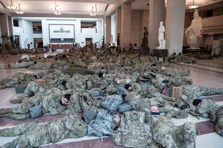 Los miembros de la Guardia Nacional descansan en el Centro de Visitantes del Capitolio en Washington, DC, el 13 de enero de 2021