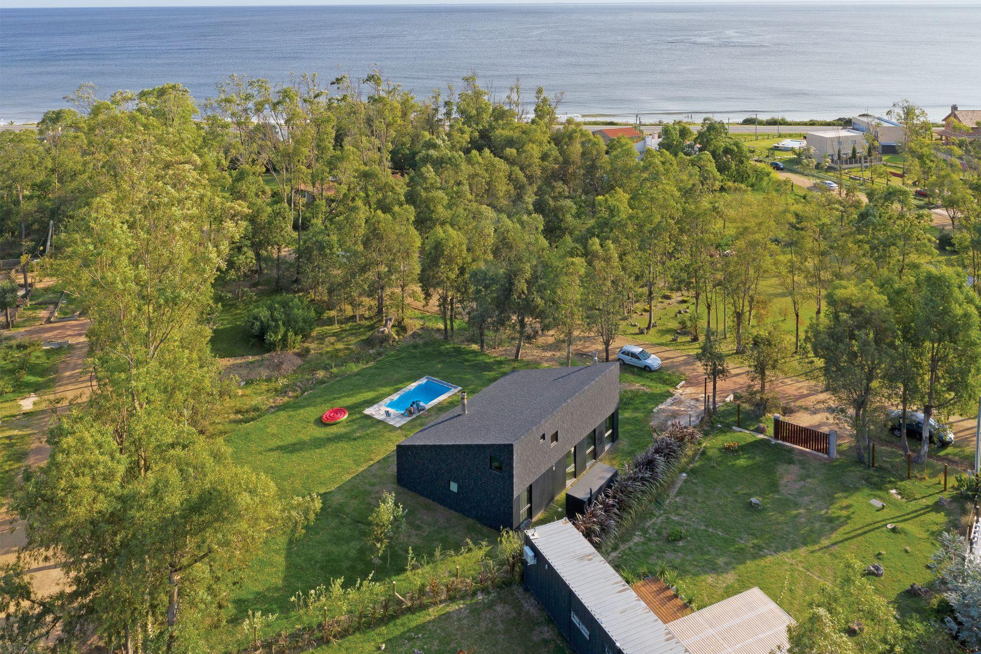 La vista aérea muestra la disposición de la casa en el lote: recostada hacia sus linderos, se abre al jardín con pileta de fibra y solado de baldosas atérmicas. Más allá, la vista a un triángulo de espacio público arbolado.