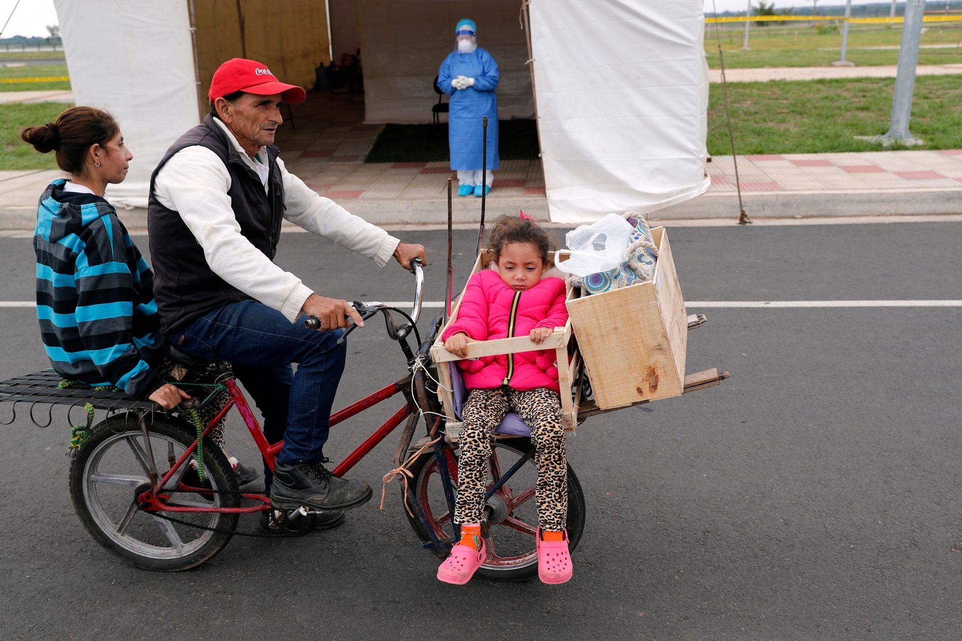 Una familia espera en su bicicleta para hacerse la prueba de COVID-19 en un sitio de prueba móvil en Asunción, Paraguay