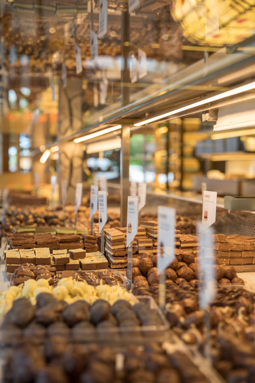 Las variedades de tabletas y trufas de chocolate de elaboración artesanal se exhiben en amplias vitrinas.
