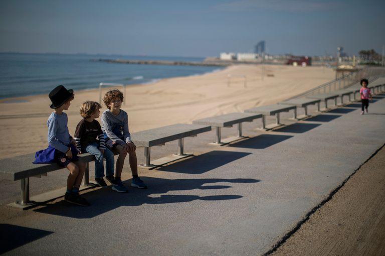 Los hermanos Pau, 4, Jan 7 y Leo, 9, se sientan cerca de la playa, donde la policía prohíbe el acceso, en Barcelona, España