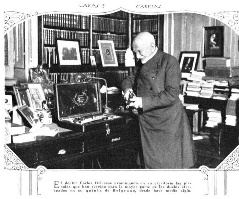 El Doctor Delcasse en su biblioteca fotografiado por la revista Caras y Caretas. Según el epígrafe, examinaba las pistolas utilizadas en los duelos de su casa