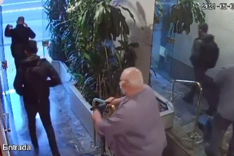 El encargado del edificio observa a los dos hombres retirarse del edificio sin saber que se trataba de delincuentes que acababan de robar en uno de los departamentos.