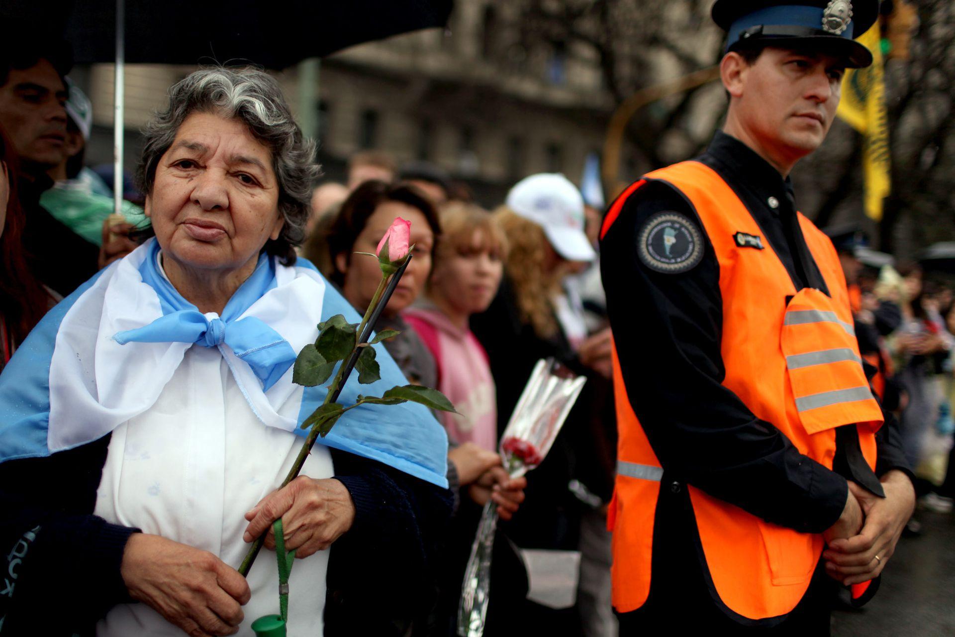 Mujeres con banderas y flores esperan para despedirse del expresidente