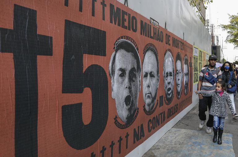 Una niña señala un mural con el rostro del presidente brasileño Jair Bolsonaro durante una protesta por su manejo de la pandemia del COVID-19 en la avenida Paulista, en Sao Paulo, Brasil, el sábado 19 de junio de 2021. (AP Foto/Marcelo Chello)