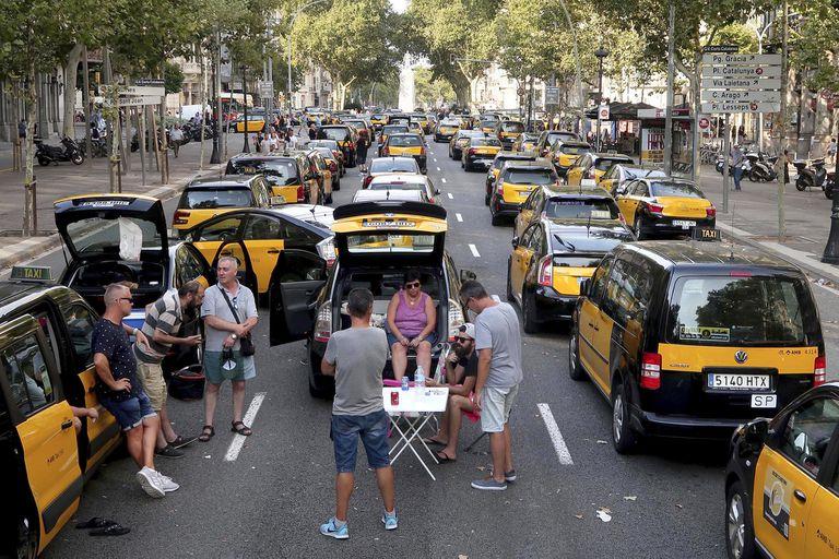 El agresivo modelo de negocios de empresas como Uber o Rappi se basa en la fiebre inversora y la felicidad del consumidor; su contracara son las fuertes pérdidas y la evasión de las regulaciones laborales. En la imagen, taxistas protestan contra Uber y Cabify en la Gran Vía de Barcelona, en julio de