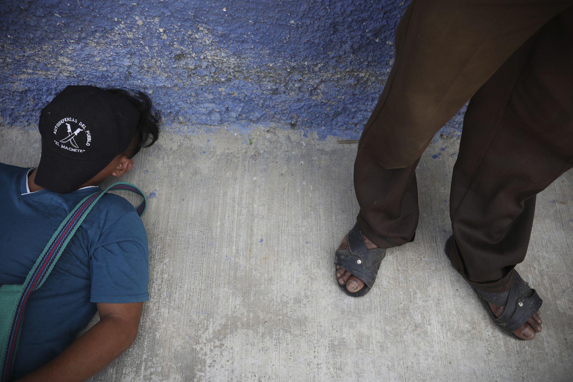 """Un miembro de """"El Machete"""" duerme una siesta en la acera mientras espera afuera durante una reunión entre autoridades locales y líderes del grupo de autodefensas en Pantelho, estado de Chiapas"""