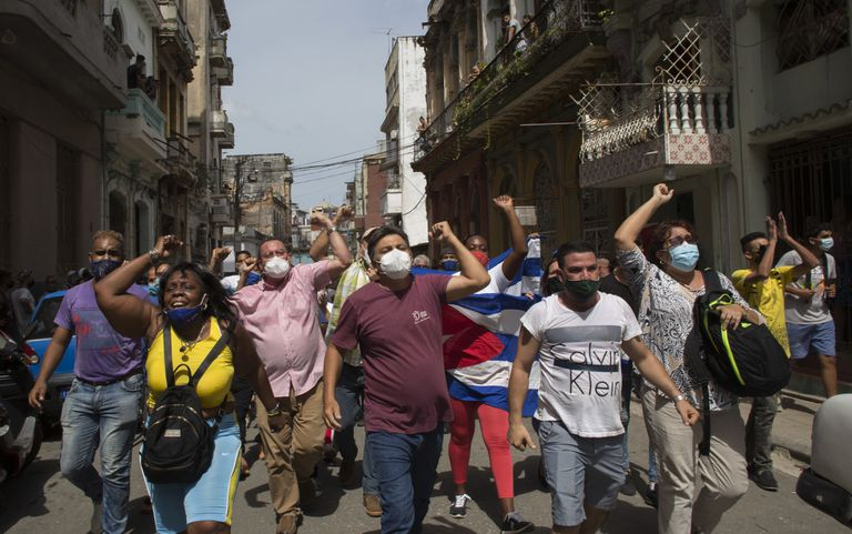 Simpatizantes del gobierno gritan consignas mientras antigubernamentales marchan en La Habana, Cuba, el domingo 11 de julio de 2021. Cientos de manifestantes salieron a las calles en la capital y varias ciudades de Cuba para protestar contra la escasez de alimentos y los altos precios de los productos en medio de la crisis sanitaria causada por la pandemia del nuevo coronavirus. (AP Foto/Ismael Francisco)