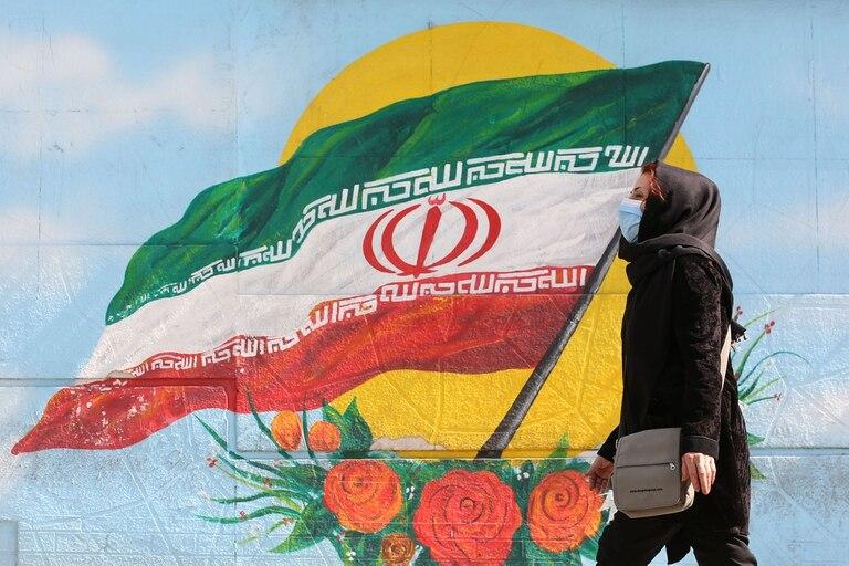 Una mujer pasa frente a un mural con la bandera de Irán, un país afectado al mismo tiempo por la pandemia y las sanciones debidas a su programa nuclear