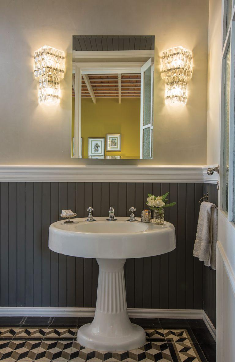 Un detalle del baño principal, donde resaltan dos apliques originales de los 50. El lavatorio de pie es de demolición y el machimbre y las cenefas están dispuestos a la manera inglesa.