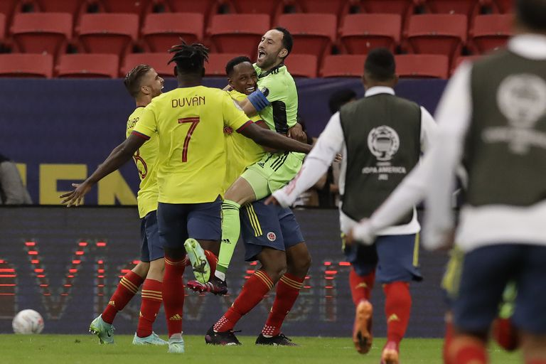 Colombia's goalkeeper David Ospina, center right, and , teammate Yerry Mina, center, celebrate after defeating Uruguay 4-2 in a penalty shootout during a Copa America quarterfinal soccer match at the National stadium in Brasilia, Brazil, Saturday, July 3, 2021. (AP Photo/Bruna Prado)