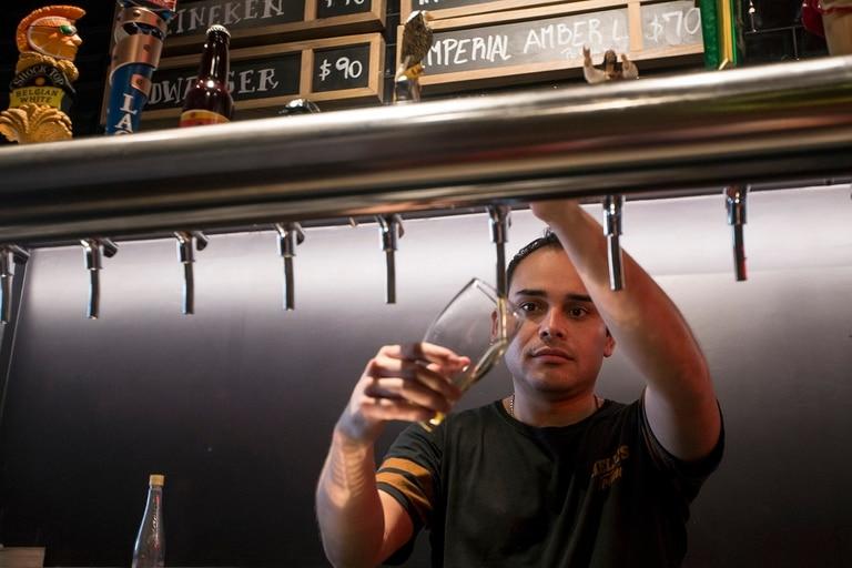 Henry Barrera, 29, de Bogota, Colombia, vino a la Argentina hace 6 años. Hoy es la cara sonriente detrás de la barra de Hell's, la pizzería de culto que abrió hace tres meses en Palermo.