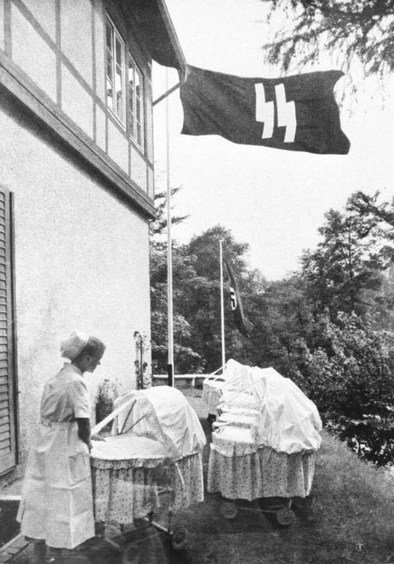 Una enfermera cuida a un bebé al aire libre mientras flamea una bandera con las runas SS