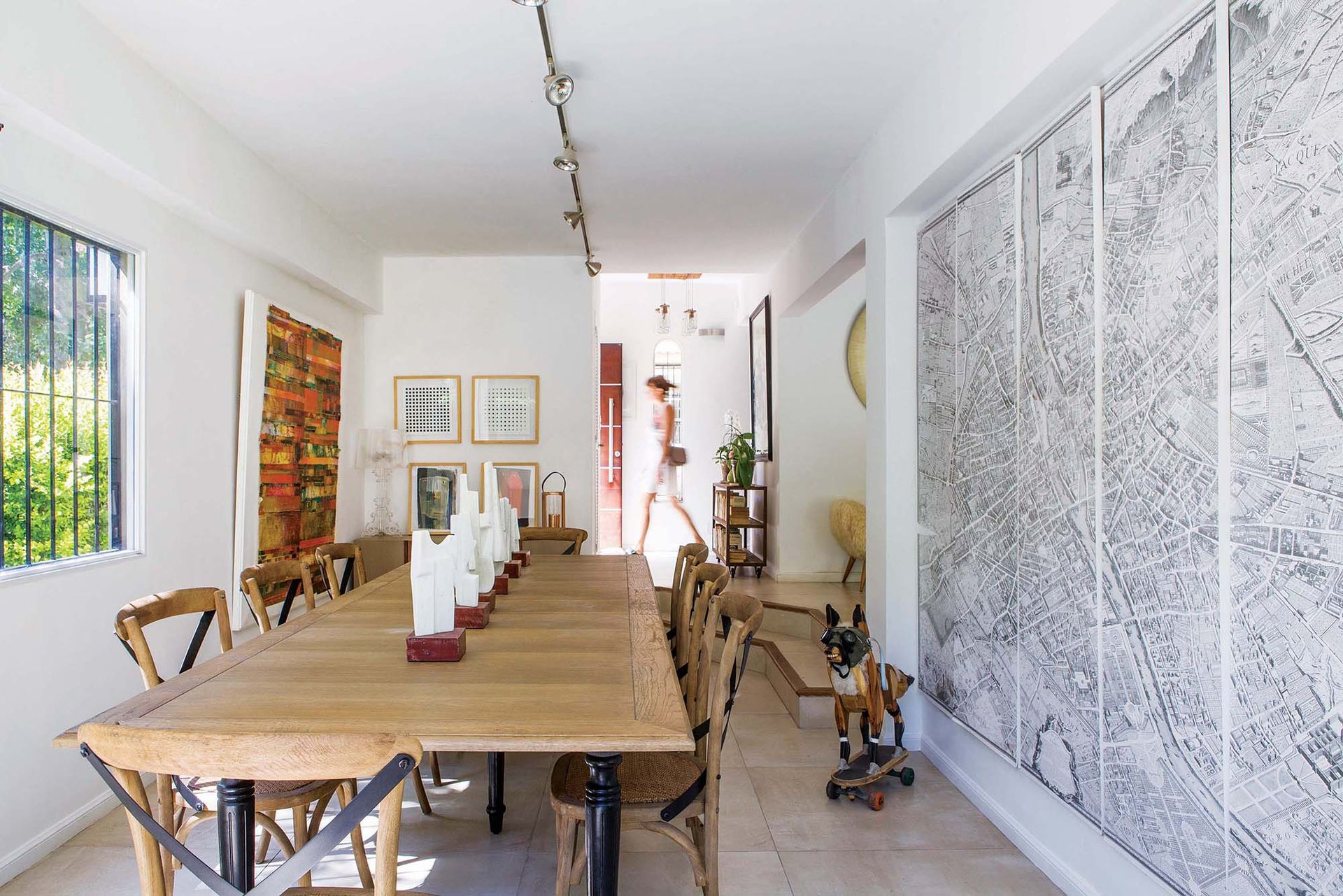 """Sobre la mesa, esculturas de la serie """"Ajedrez"""", de Valeria Budassof. En el piso, """"Zorro enmascarado"""", de David Klauser. Daguerrotipo políptico de un mapa histórico de París (Harturo)."""
