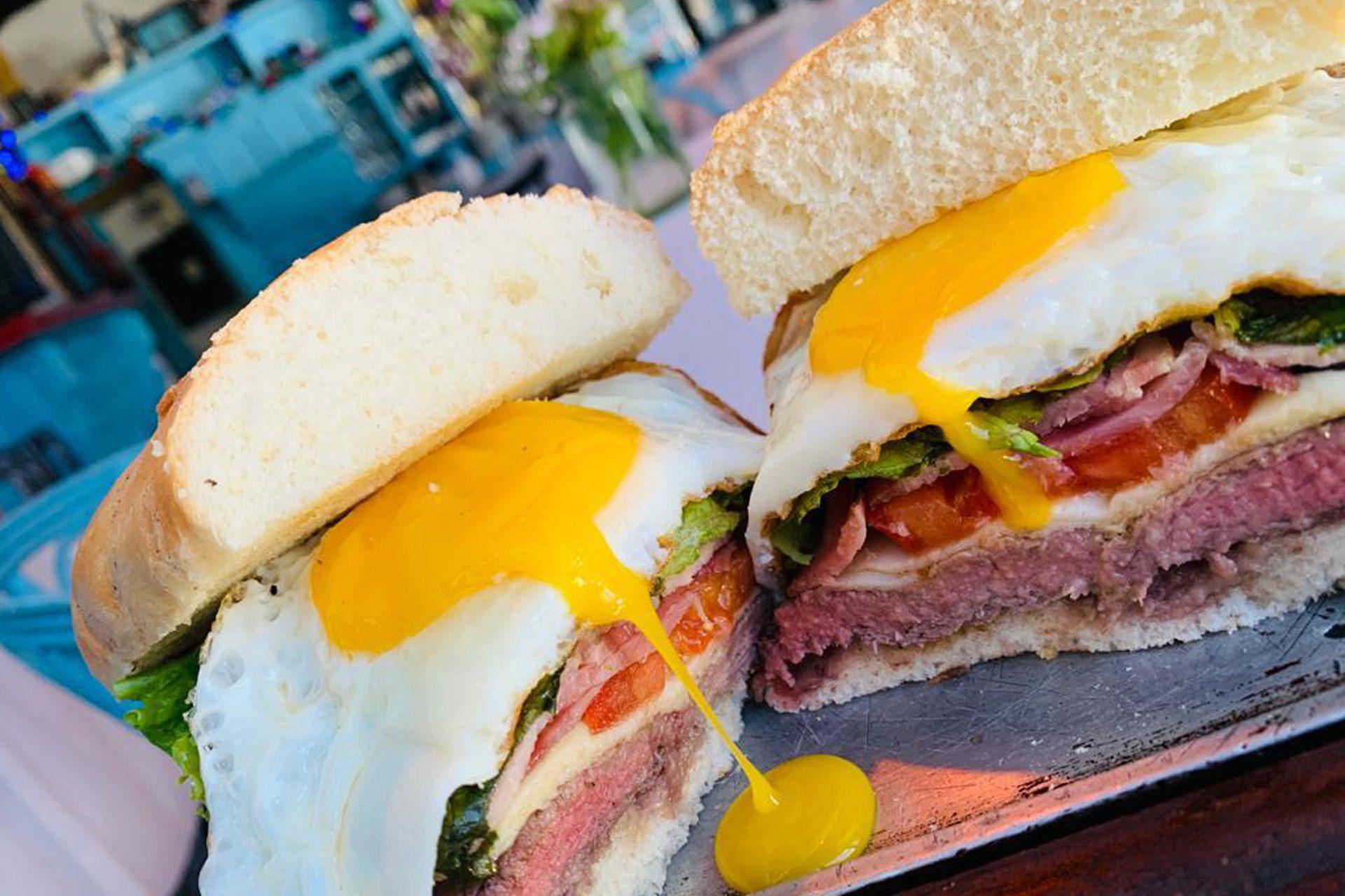 Queso, panceta ahumada, tomates confitados, rúcula orgánica y un huevo de campo frito con la yema bien cremosa forman parte del sándwich de chivito de Bar de Carnes.