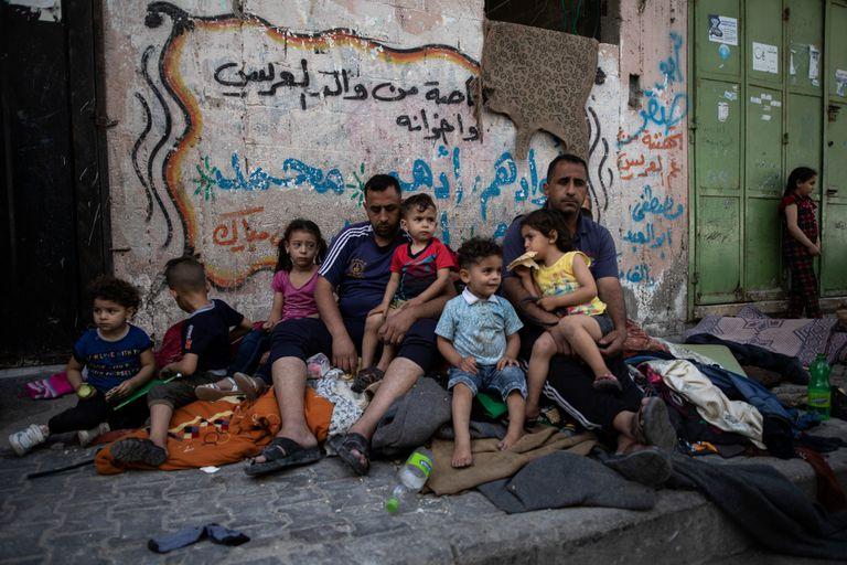 Una familia en Gaza se sienta afuera de su casa después de que fue alcanzada por un ataque aéreo israelí