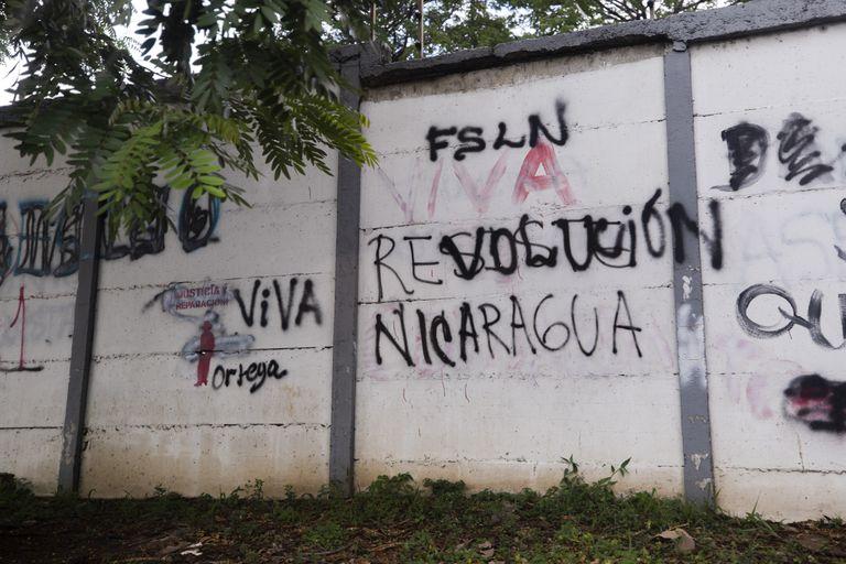 """Lucha de graffitis en Managua: una pared con un mensaje que alguna vez decía  """"Resiste Nicaragua"""" fue pintada con otro mensaje que ahora dice """"Viva la revolución"""""""
