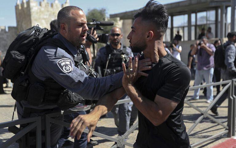 Un policía israelí intenta detener a un hombre palestino durante los disturbios en la marcha organizada por movimientos israelíes nacionalistas en Jerusalén Este el 15 de junio de 2021