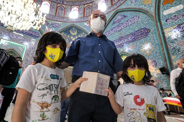 Un votantes y sus hijos en Teherán