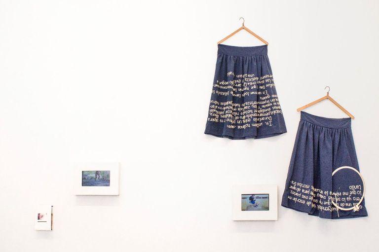 Faldas con textos íntimos bordados en hilo dorado, de Emilia Molina, en la muestra de Urquiza