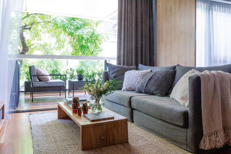 El sofá tapizado en lino de 2x0,90m se divide en dos. Es bajo, para no invadir el espacio y teniendo en cuenta la altura de la TV, que el dueño quiso ubicar en un lugar con poco protagonismo. Alfombra de pura lana (Elementos Argentinos). Jarrón con flores (Otra Sudestada Flores).