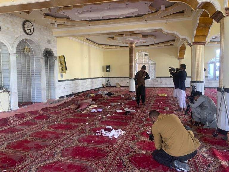 Periodistas afganos toman fotos y videos dentro de una mezquita donde explotó una bomba el viernes 14 de mayo de 2021 en el distrito Shakar Dara de Kabul, Afganistán. La bomba estalló durante las oraciones del viernes y mató a 12 fieles, dijo la policía afgana. (AP Foto/Rahmat Gul)