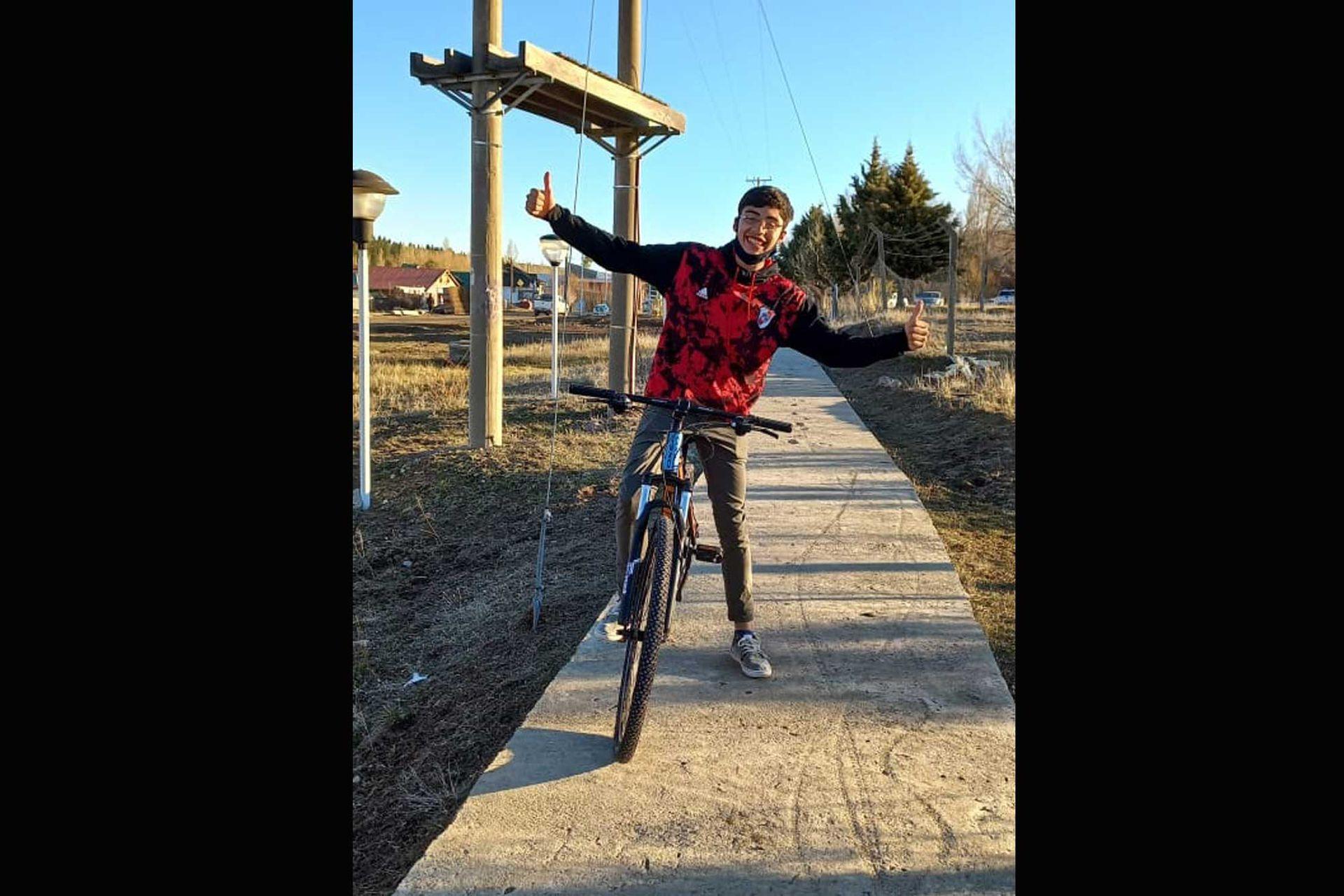 Tiziano, con sonrisa completa, con la bicicleta nueva que le donaron para que pueda ir a la escuela