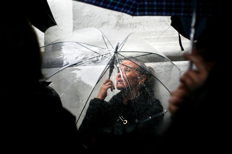 Una mujer busca reparo de la lluvia durante una marcha del colectivo #NiUnaMenos, el 19 de octubre de 2016, en Buenos Aires