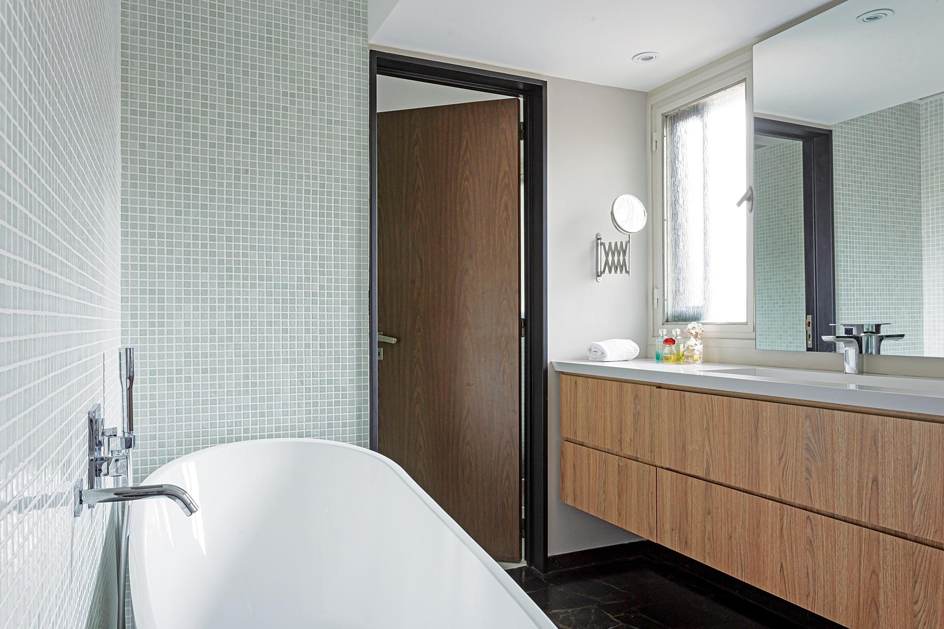Rediseñado para generar una mesada con doble bacha corrida, bañera y ducha, el baño está revestido con antiguas venecitas de vidrio, que se mandaron a armar especialmente.