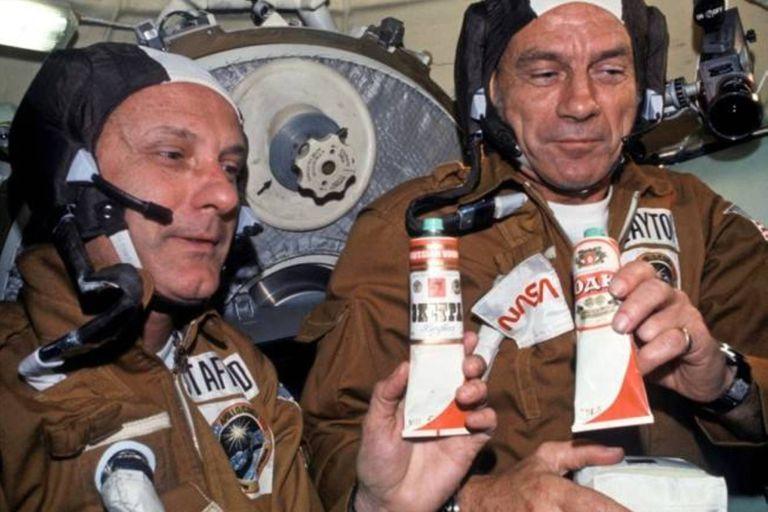 """Los astronautas Stafford y Slayton sostienen los tubos de """"vodka"""" a bordo del Soyuz"""