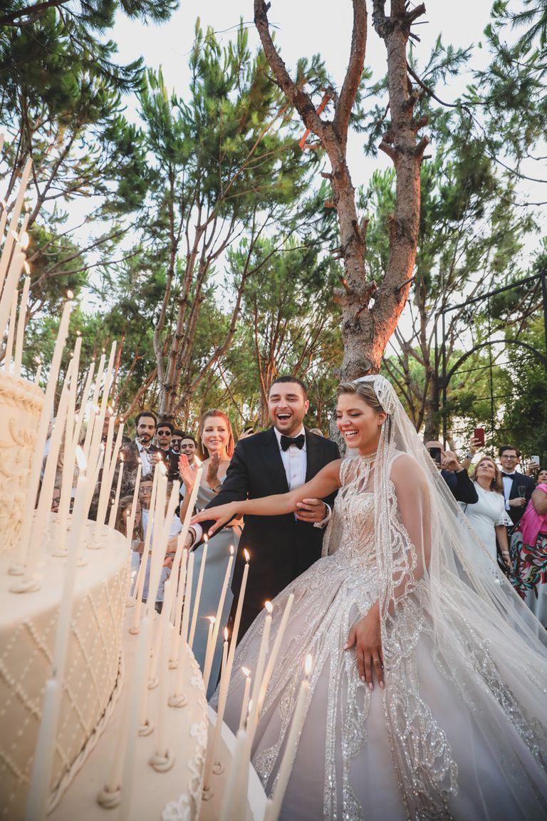 Los novios cortan la torta de boda de nueve pisos y un metro y medio de altura adornada con 365 velas, una por cada día del año.