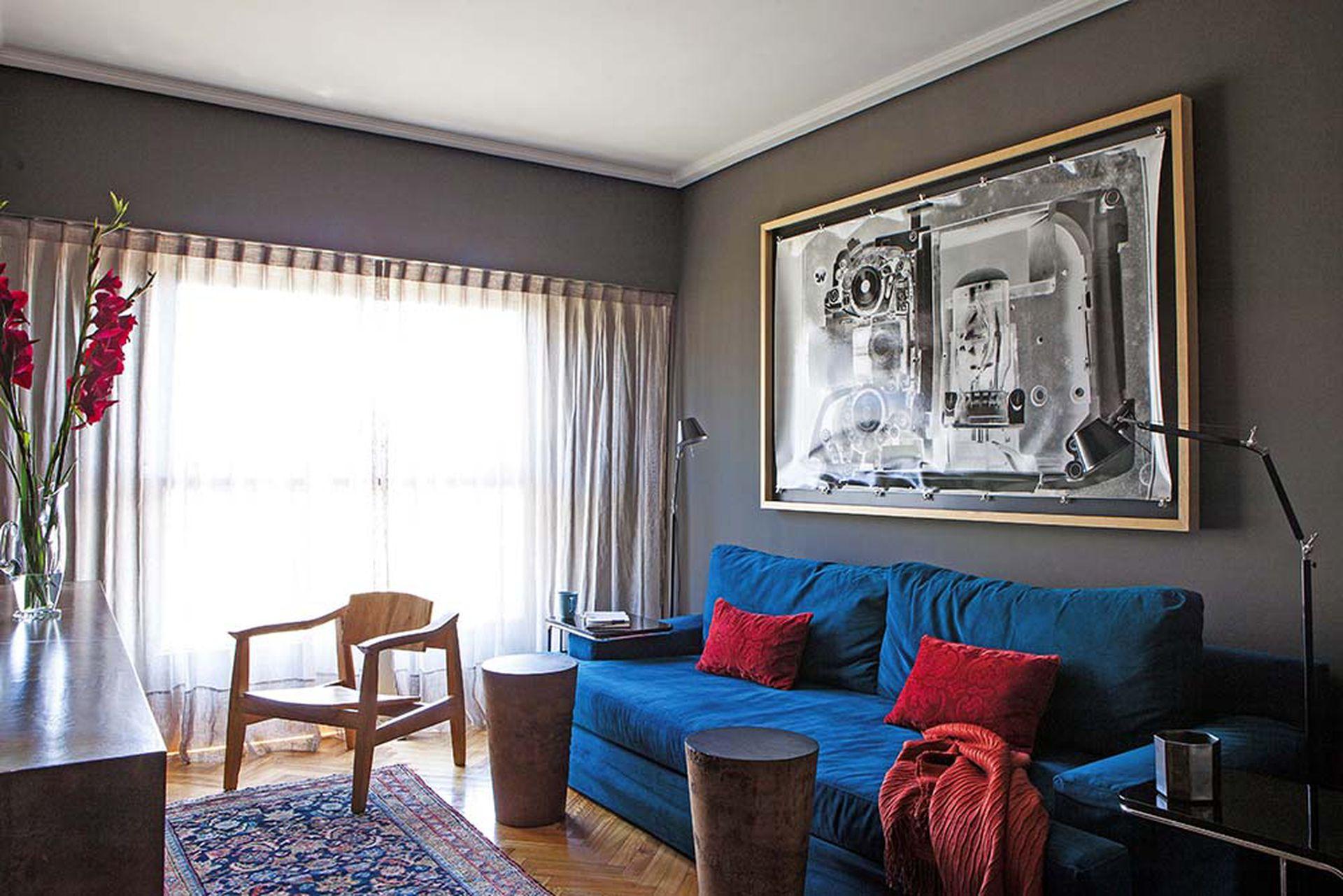 En la pared, una gran foto de una cámara antigua sostenida con ganchos de escritorio.