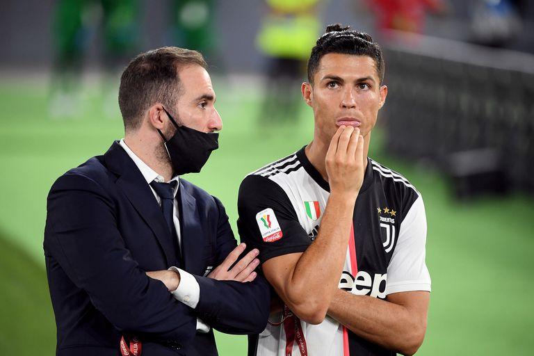 Gonzaló Higuaín, ausente por una lesión, conversa con Cristiano Ronaldo tras el final del partido