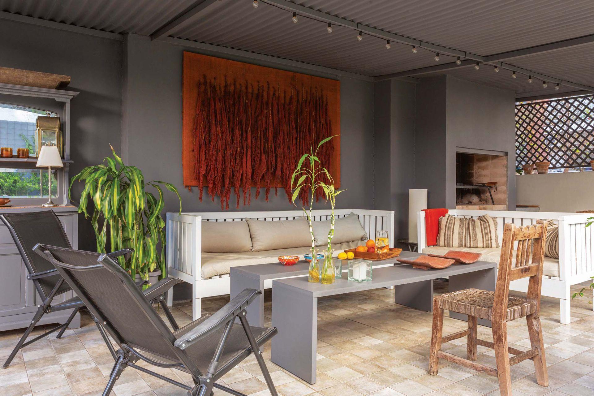 Dos camastros de madera pintados de blanco, dos mesas de centro de MDF hechas por los dueños y un par de sillas reclinables (Easy) rodean un tapiz en telar de María Inés Miranda.