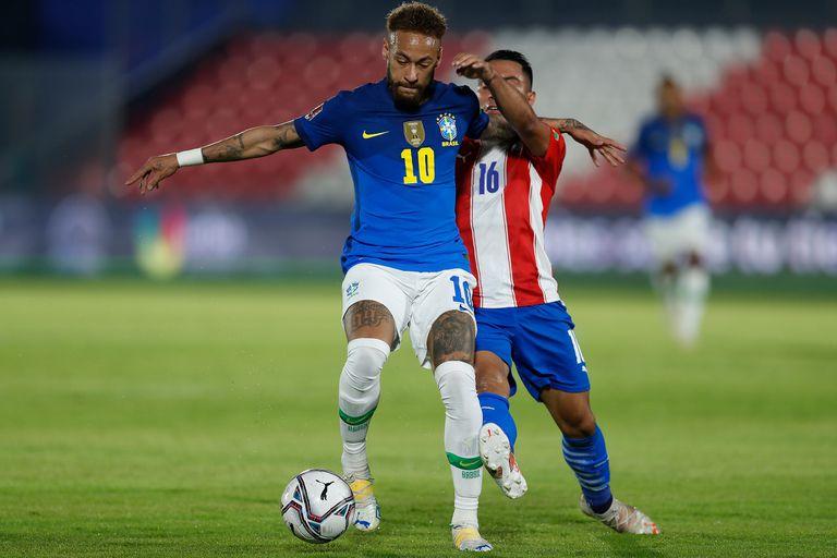 Neymar y Ángel Cardozo en pos del balón en Paraguay 0 vs. Brasil 2; el hábil atacante publicó el comunicado que aglutina la opinión del plantel que será local en la Copa América.