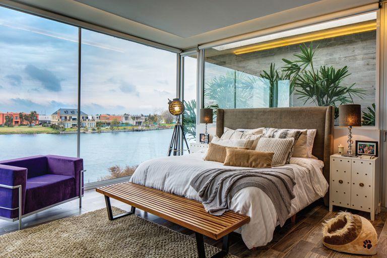 La suite tiene la mejor vista a la laguna. El respaldo de la cama en lino oscuro acompaña el estilo de Hollywood de las mesas de luz con tachas, modelo de años 50. Contra el gran ventanal descansa un farol marino convertido en lámpara de pie. Al costado de la cama está la cucha de su caniche.