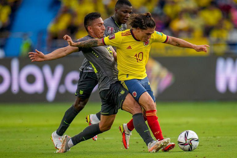 El ecuatoriano Ángel Mena marca al colombiano Juan Quintero (10) en el partido de las eliminatorias del Mundial, el jueves 14 de octubre de 2021, en Barranquilla.
