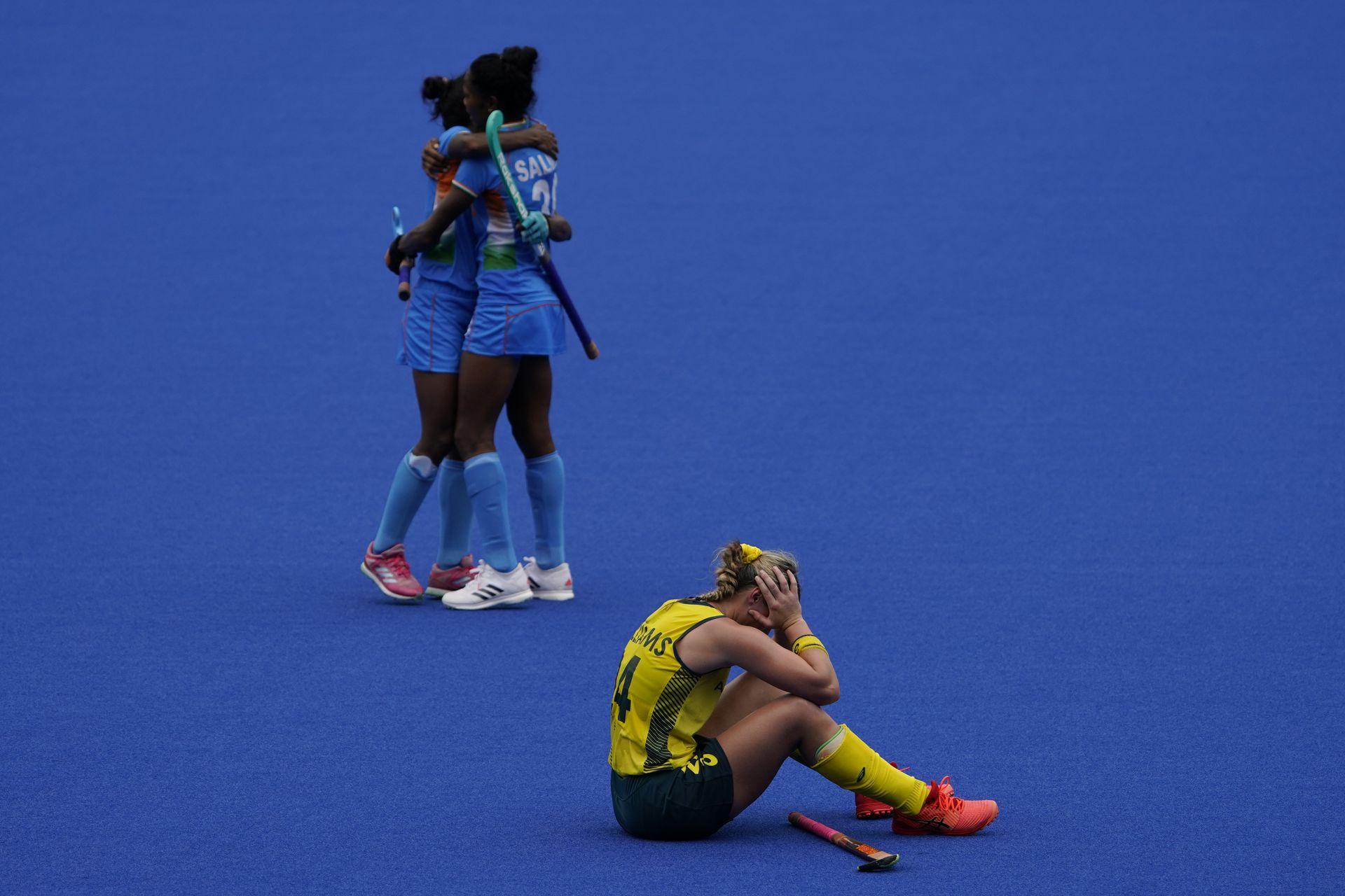 La australiana Mariah Williams, abajo, se sienta en la cancha después de perder su partido de hockey sobre césped femenino contra India