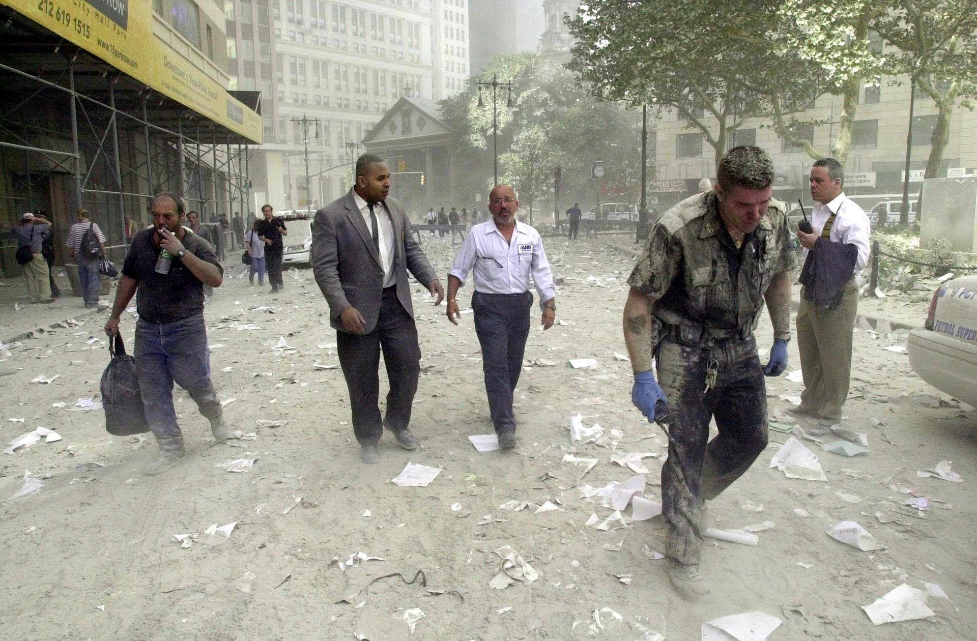 Un oficial de policía y varios ciudadanos caminan por las calles cubiertas de escombros cerca de las torres del World Trade Center